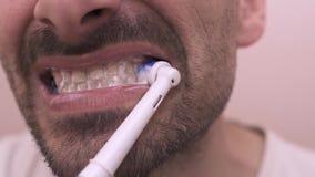 L'uomo barbuto che pulisce i suoi denti nello specchio apre la bocca video d archivio