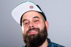 L'uomo barbuto con il berretto da baseball sta sorridendo Immagine Stock Libera da Diritti