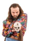 L'uomo barbuto con un cranio Fotografia Stock