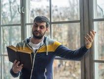 L'uomo barbuto del poeta legge un libro con un'espressione Immagini Stock Libere da Diritti