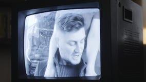 L'uomo barbuto di canto con i baffi è visualizzato sullo schermo di retro set televisivo video d archivio