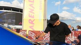L'uomo barbuto di vista laterale disegna i modelli dell'oro sull'automobile blu royalty illustrazione gratis