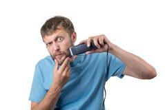 L'uomo barbuto divertente rade il suo regolatore della barba, su fondo bianco Immagine Stock