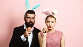 L'uomo barbuto e bella la donna che durano sulle orecchie mangiano le carote su fondo rosa Coppie alla moda con le orecchie su un archivi video