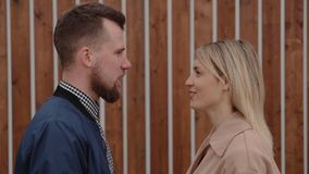 L'uomo barbuto e la donna bionda stanno guardando l'un l'altro e sincrono di conversazione stock footage