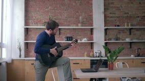 L'uomo barbuto felice del chitarrista che impara lo strumento musicale messo insieme gioco utilizza il computer portatile con la  video d archivio