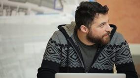 L'uomo barbuto felice si siede alla tavola e lavora al computer portatile in ufficio archivi video