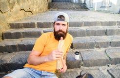L'uomo barbuto gode del fondo urbano dell'alimento della via Rottura della presa per mangiare spuntino Concetto urbano della cult fotografia stock