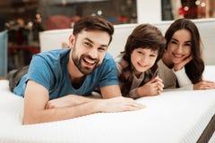 L'uomo barbuto, insieme alla suoi bei moglie e figlio, si rilassa sul materasso nel deposito fotografia stock