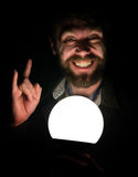 L'uomo barbuto nello scuro, tenente davanti ad una lampada, esprime le emozioni differenti la mostra sfoglia sul metallo pesante  Fotografie Stock Libere da Diritti