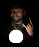 L'uomo barbuto nello scuro, tenente davanti ad una lampada, esprime le emozioni differenti la mostra sfoglia sul metallo pesante  Immagini Stock
