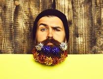 L'uomo barbuto, pantaloni a vita bassa premurosi caucasici brutali con la decorazione del regalo stars Fotografia Stock