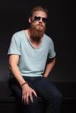L'uomo barbuto se vi siede ed esamina Immagine Stock