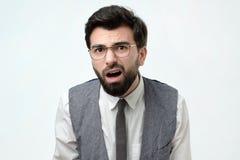 L'uomo barbuto sospettoso guarda dubbioso, essendo non decisivo, fa lo smorfia, prova a trovare la soluzione fotografia stock