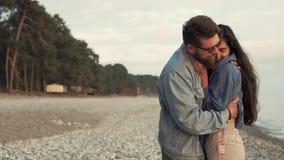 L'uomo barbuto sta baciando tenero la donna cara fragile sulla spiaggia nel tempo del tramonto video d archivio