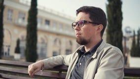 L'uomo barbuto sta godendo dell'aria fresca della città della molla, sedentesi su un banco all'aperto stock footage
