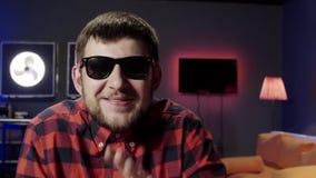 L'uomo barbuto sveglio parla ed attivamente applaude in studio ammobiliato moderno scuro archivi video