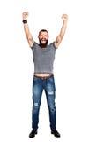 L'uomo barbuto tatuato bello emozionante con le armi si è alzato nei succes Fotografia Stock Libera da Diritti