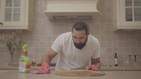 L'uomo barbuto in una maglietta bianca e nei guanti di gomma tira il detersivo sulla tavola e lo pulisce con uno straccio Un tipo stock footage