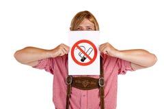 L'uomo bavarese tiene il segno di nessun-fumare-regola fotografia stock