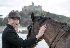 L'uomo bello, cavaliere del cavallo maschio pets il suo cavallo sulla spiaggia, il cappuccio piano tradizionale d'uso, i pantalon Fotografia Stock Libera da Diritti