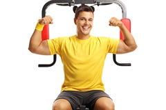L'uomo bello che mostra il bicipite muscles su una macchina di forma fisica fotografia stock