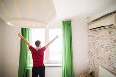 L'uomo bello che sveglia nelle mani in aumento del letto alla finestra di mattina con la sensibilità fresca si rilassa Fotografie Stock