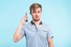 L'uomo bello con uno sguardo stanco ed irritato prende il telefono a partire dal suo orecchio che prova a muoversi a partire dai  Immagine Stock Libera da Diritti