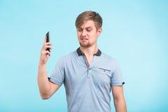 L'uomo bello con uno sguardo stanco ed irritato prende il telefono a partire dal suo orecchio che prova a muoversi a partire dai  Fotografia Stock