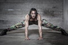 L'uomo bello del muscolo porta i pantaloni del cammuffamento Fotografia Stock