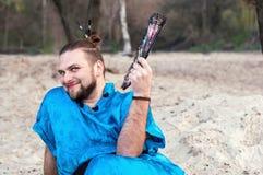 L'uomo bello del transsessuale con compone, panino dei capelli che si siede sulla sabbia in kimono blu, sorridente e tenente il v fotografia stock