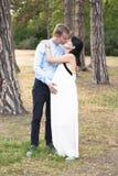 L'uomo bello e la bella moglie incinta stanno abbracciando e baciando all'aperto fotografia stock