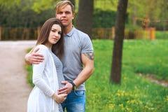 L'uomo bello e la sua bella moglie incinta sono abbraccianti e sorridenti mentre stanno nel parco immagine stock