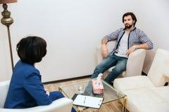 L'uomo bello e rilassato sta sedendosi davanti allo psicologo e sta esaminandola È molto sicuro Il tipo è a sorridente Fotografia Stock