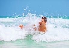 L'uomo bello gode di di nuotare nelle onde del mare immagine stock libera da diritti