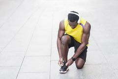 L'uomo bello lega i laccetti sulle scarpe da tennis prima di correre Fotografie Stock