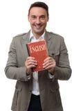 L'uomo bello sorridente tiene il manuale inglese Fotografie Stock Libere da Diritti