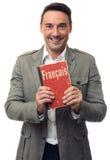 L'uomo bello sorridente tiene il manuale inglese Immagine Stock Libera da Diritti
