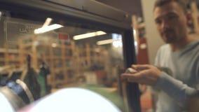 L'uomo bello sta prendendo la bottiglia di vino bianco dalle bottiglie di vino del frigorifero sta risiedendo nel posto freddo archivi video