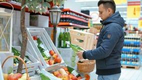 L'uomo bello sta scegliendo il sidro di Apple nel supermercato archivi video