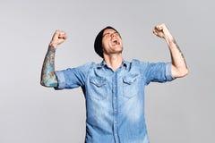 L'uomo bello sta urlando e gode del successo sulla parete bianca Immagine Stock