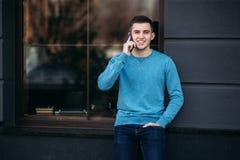 L'uomo bello sta utilizzando il telefono sulla via fotografia stock