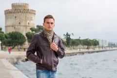 L'uomo bello, turistico, sta vicino ad una torre bianca nel centro Salonicco, Grecia davanti ad un mare immagini stock libere da diritti