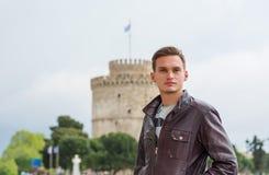 L'uomo bello, turistico, sta vicino ad una torre bianca nel centro Salonicco, Grecia fotografia stock