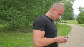 L'uomo bello utilizza il suo telefono cellulare all'aperto in parco, movimento lento di vista laterale video d archivio