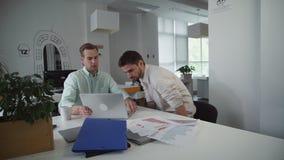 L'uomo bello viene in ufficio che si siede alla tavola che parla con i colleghi stock footage