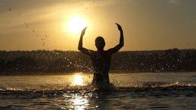 L'uomo biondo alza l'acqua del lago per intrattenere al tramonto nel slo-Mo video d archivio