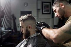 L'uomo brutale si siede nella sedia ad un negozio di barbiere Il barbiere in guanti neri rade i capelli dell'uomo alla parte post immagine stock