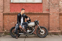 L'uomo brutale si siede sulla motocicletta di abitudine del corridore del caffè fotografia stock libera da diritti