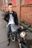 L'uomo brutale si siede sulla motocicletta di abitudine del corridore del caffè immagini stock libere da diritti